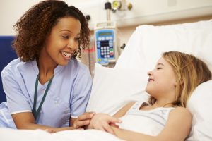 Nurse Sitting By Young Girl's Bed In Hospital